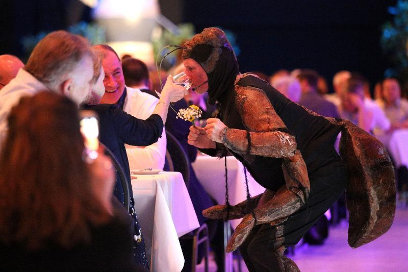 Ein Schauspieler in einem Käferkostüm bezieht die Gäste mit ins Schauspiel mit ein.